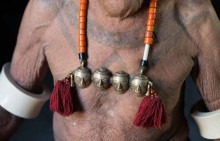 A Naga elder wears a necklace with brass skulls, signifying the number of heads taken during his headhunting days.